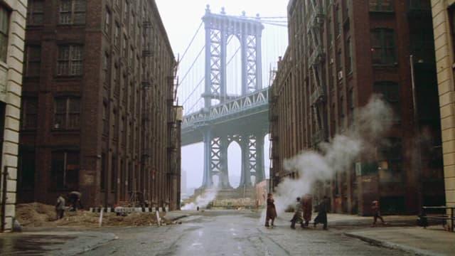 Mehere Personen gehen durch eine Strasse in new York. Im Hintergund ist eine riesige Brücke zu sehen. Bildausschnitt aus «Once Upon a Time in America».