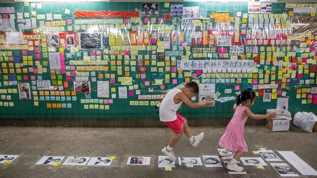 Zwei chinesische Kinder hüpfen. Sie spielen Himmel und Hölle.