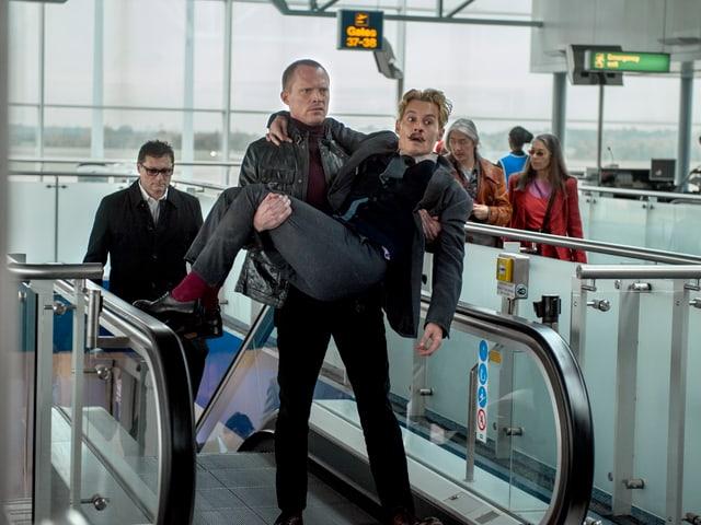 Jock trägt Mortdecai über die Rolltreppe im Flughafen.