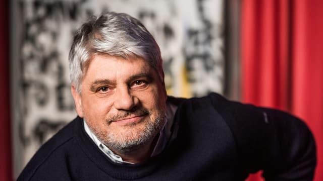 Mann mit grauen Haaren, Pulli und Hemd drunter sitzt vor einer Rot-schwar-weissen Wand und lächelt mit geschlossenem Mund in die Kamera.