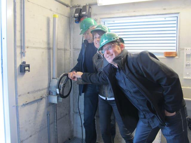 Drei Personen mit grünen Bauhelmen drehen gemeinsam an einem Rad, welches die Schleuse öffnet.
