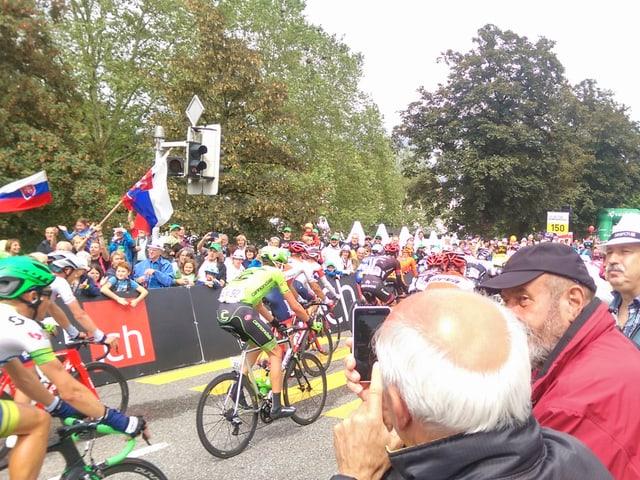 Fans feuern die Radrennfahrer an.