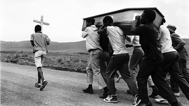 Man sieht schwarze Jugendliche, die einen Sarg tragen. Ein Jugendlicher trägt ein Kreuz.