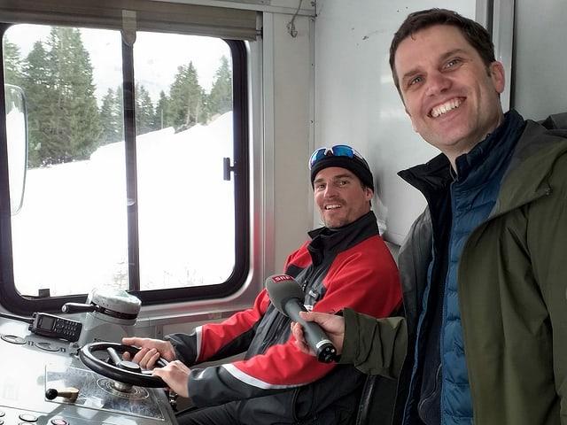 Ein Lokführer und ein Reporter in einem Führerstand.