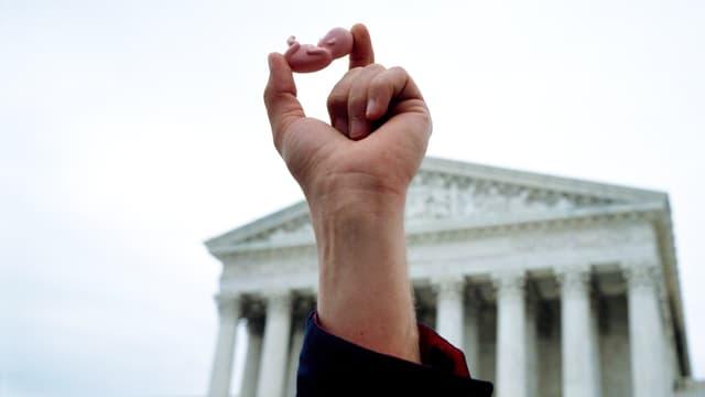 Eine Hand hält ein kleines Plastikmodell eines Fötus in die Luft. Dahinter ein Gerichtsgebäude.