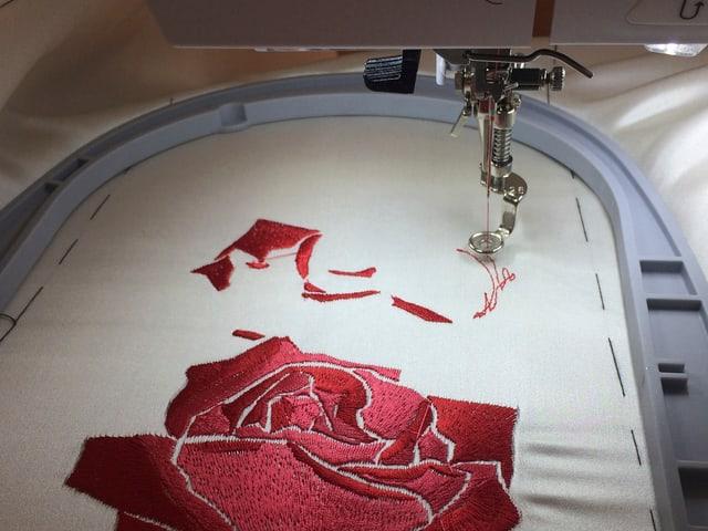 Mit der Nähmaschine gestickte Blumen auf weissem Stoff