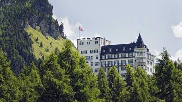 Ein edles Hotel-Gebäude thront über einem Wald.
