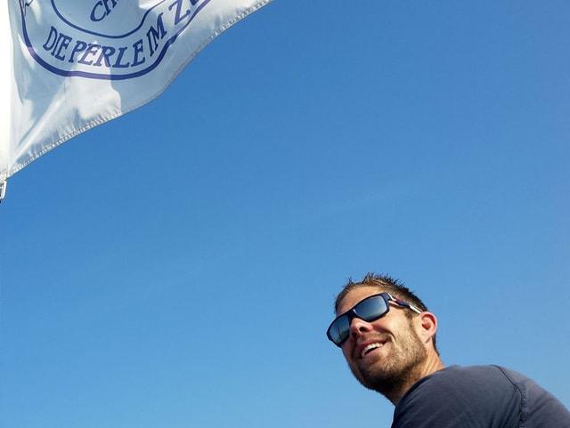 Mann mit Sonnenbrille unten rechts im Bild, oben links ist eine weiss-blaue Fahne.