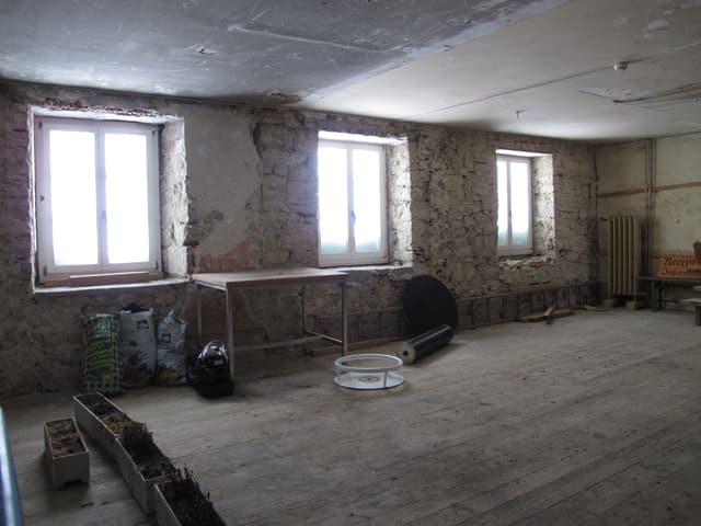 Ein Raum mit Bretterboden und ohne verputze Wände.