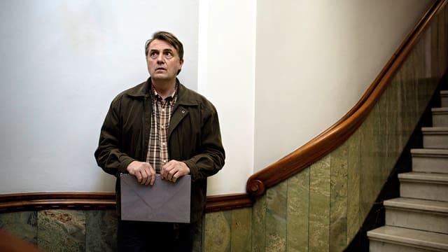 Ein Mann mit einer Mappe in der Hand steht im Treppenhaus.