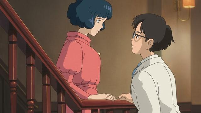 Eine junge Frau steht am Ende einer Treppe, wo sie einem jungen Mann in die Augen schaut.