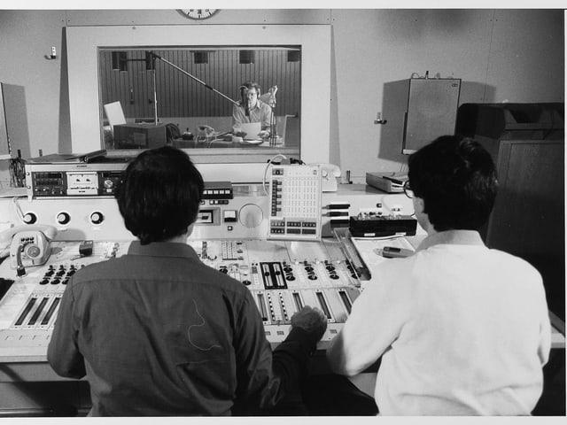 Zwei Männer sitzen hinter einem Mischpult, weiter hinten ein Mann hinter dem Mikrofon.