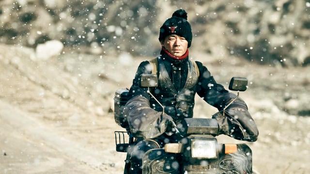 Ein Mann auf einem Motorrad. Es schneit.