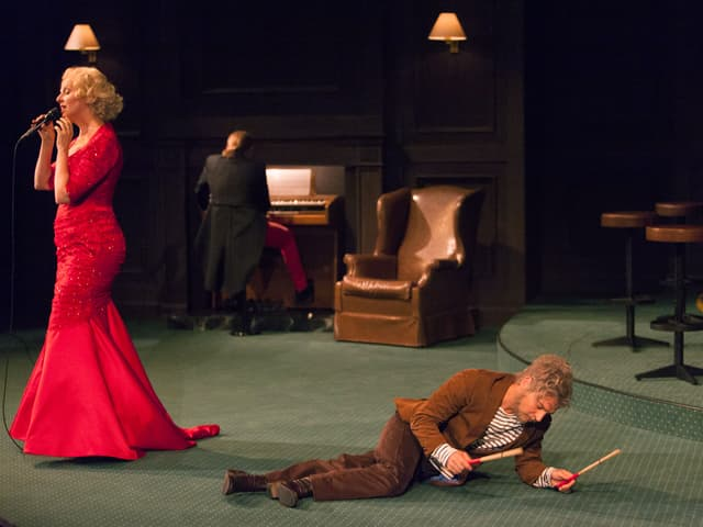 Frau in roter Robe steht und singt, Mann liegt am Boden mit Drummersticks.