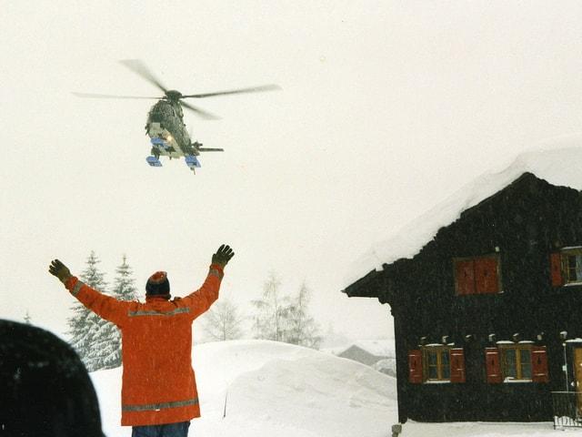 Helikopter wird von Mann in oranger Jacke eingewiesen.