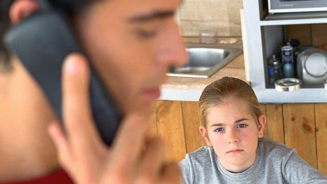Ein Vater führt ein Telefongespräch in Anwesenheit seines Sohns