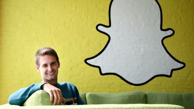 Snapchat-Chef Evan Spiegel in einem Sofa sitzend, rechts von ihm das Logo des Unternehmens