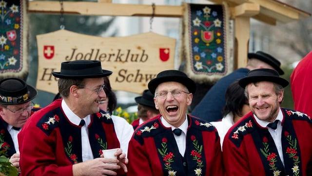 Drei Jodler sitzen zusammen lachend auf einer Bank.