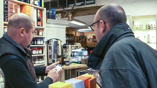 SRF-Redaktor Reto Widmer gibt Jens Müller sein Smartphone an der Kassen-Theke, um den Gutschein für den Kaffee einzulösen.