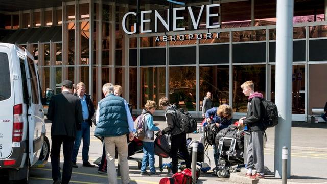Passagiere entladen Gepäck vor dem Terminal des Flughafens Genf