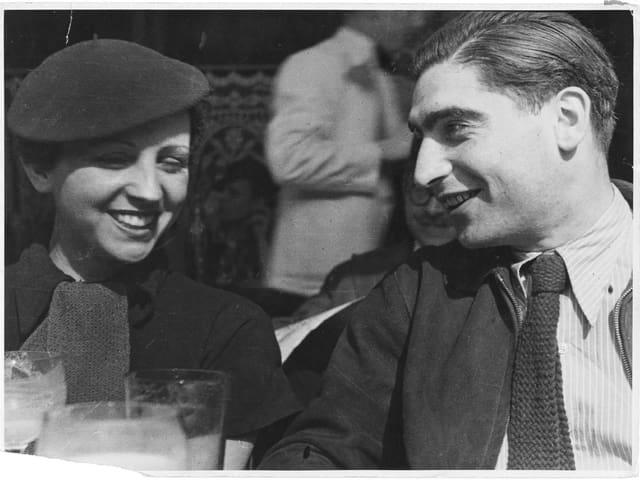 Schwarzweissaufnahme: Taro und Capa lachend in einem Café.