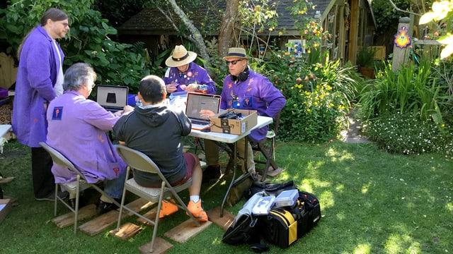 Fünf Herren mit violetten Jacken in einem Garten.
