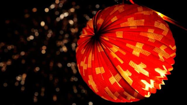 In der rechten Bildhälfte ist ein Lampion zu sehen. Das Lampion ist von innen her beleuchtet, wie es sich für ein Lampion gehört. Das Lampion ist rund. Es ist rot, mit vielen weissen Schweizerkreuzen. Hinter dem Lampion und in der linken Bildhälfte ist im dunkeln Himmel schwach noch ein Feuerwerk zu erkennen. Der Fotograf hat hier sehr schön mit Schärfe und Unschärfe gespielt.