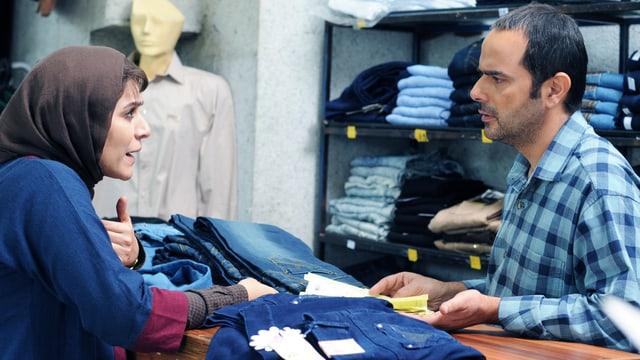 Frau diskutiert mit Mann. Auf dem Tisch liegen Jeans.