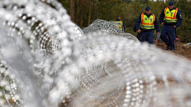 Ungarische Grenzwächter stehen hinter Rollen von Stacheldraht.
