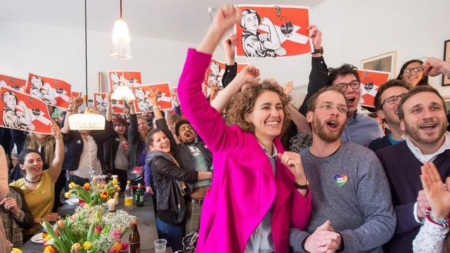 Junge Menschen feiern und halten Plakate in die Luft, auf der eine junge Frau Muskeln zeigt.