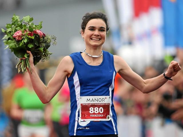 Eine Läuferin mit blauem Trägershirt.