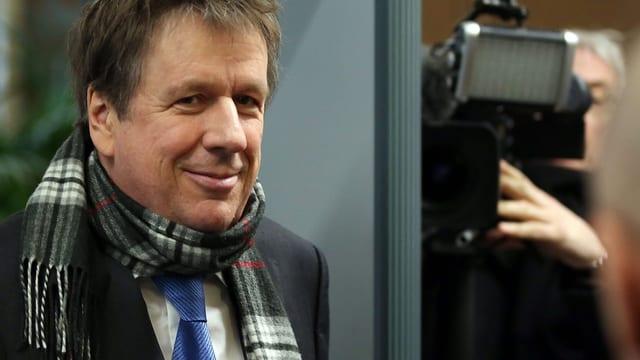 Kachelmann mit Schal lächelt in die Kamera, hinter ihm ein Kameramann.