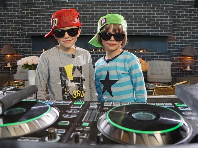 Zwei Kinder stehen an einem DJ-Pult.