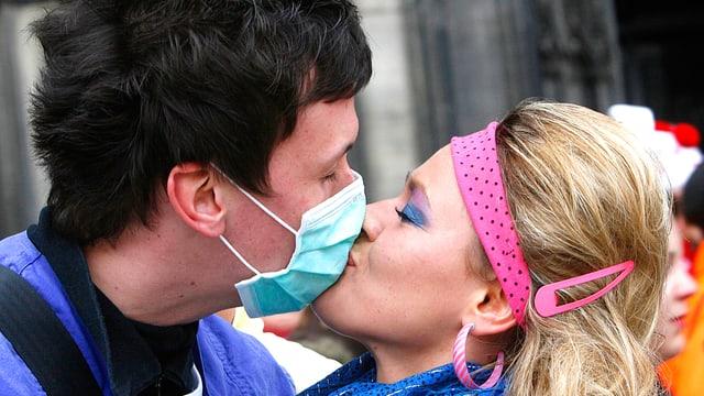 Ein Liebespaar küsst sich. Der Mann trägt einen medizinischen Anti-Grippenviren-Mundschutz.
