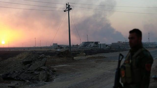 Zu sehen ist ein kurdischer Soldat, im Hintergrund Gefechtsrauch.