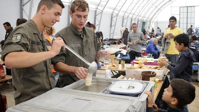Zwei Bundesheer-Soldaten schöpfen Flüchtlingen das Essen aus.
