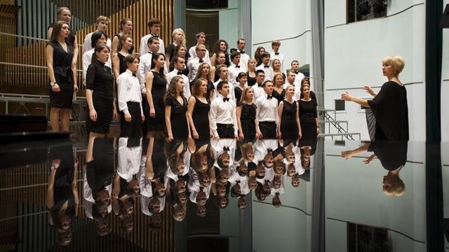 Sängerinnen, Sänger und Dirigentin spiegeln sich auf einer glatten Oberfläche.