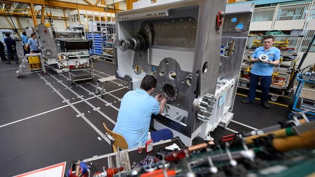 Zwei Männer arbeiten an einer Maschine.