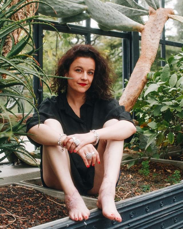 Nora Zukker sitzt Barfuss in einem Gewächshaus.