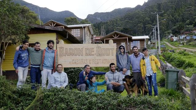 """Eine Gruppe von Menschen neben einem Schild mit der Aufschrift """"Baron de Root - Restaurant"""""""