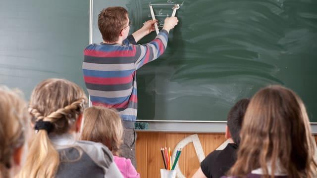 Bild aus einem Schulzimmer. Der Lehrer zeichnet an der Tafel.