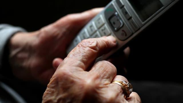 Frau mit Festnetztelefon in den Händen