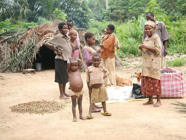 Eine Baka-Familie vor ihrer Laubhütte - die Kinder mit aufgeblähten Bäuchen.