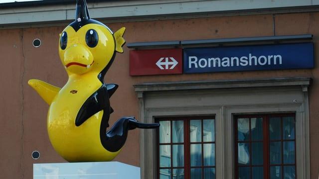 Der gelbschwarze Mocmoc, im Hintergrund der Bahnhof Romanshorn.