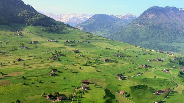 Eine Luftaufnahme einer Landschaft mit vielen vereinzelt-stehenden Bauernhäusern.