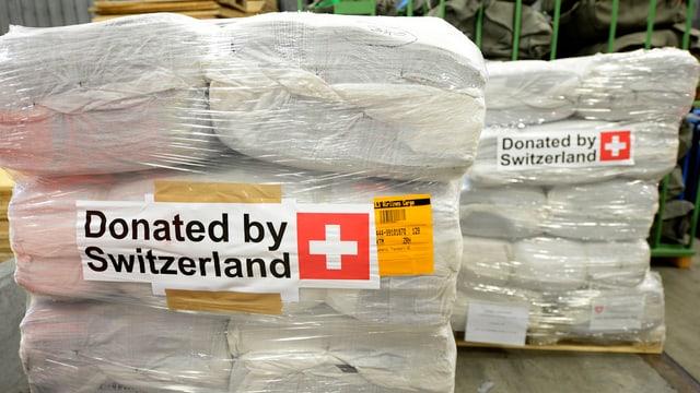 Zwei Paletten mit Hilfsgütern und der Aufschrift «Donated by Switzerland».