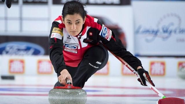 Giugadra da curling en schanuglias stumpla cun in maun il crap e cun l'auter tegna ella la scua.