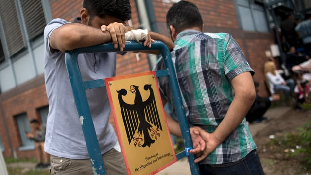 Zwei junge männliche Flüchtling warten, zu sehen ist auch das Schild des Deutschen Bundesamtes für Migration