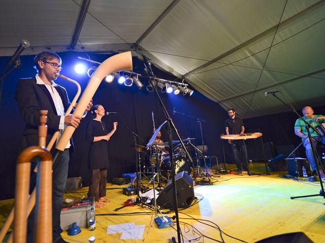 Ein Mann mit einem Alphorn und andere Musiker auf der Bühne.