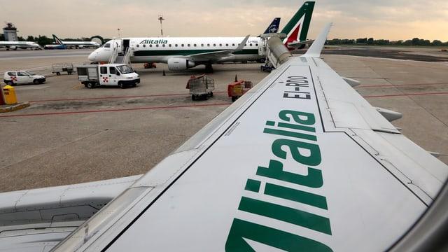 Flügel von Alitalia im Vordergrund, Flieger im Hintergrund
